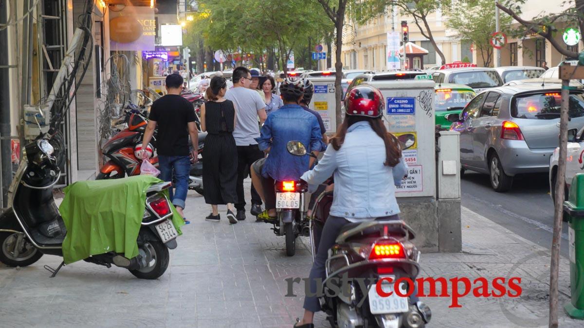 Motorbikes colonise the pavements. Saigon's tourist centre this week.