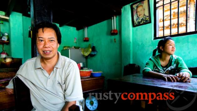 Mr Binh of Com Ga Ba Buoi. Here he sits with his daughter. His mother, Ba Buoi watches on from behind. She started the small eatery in the 1950s.