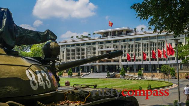 The former Presidential Palace and a replica of the tank that broke down the gates in April 1975.