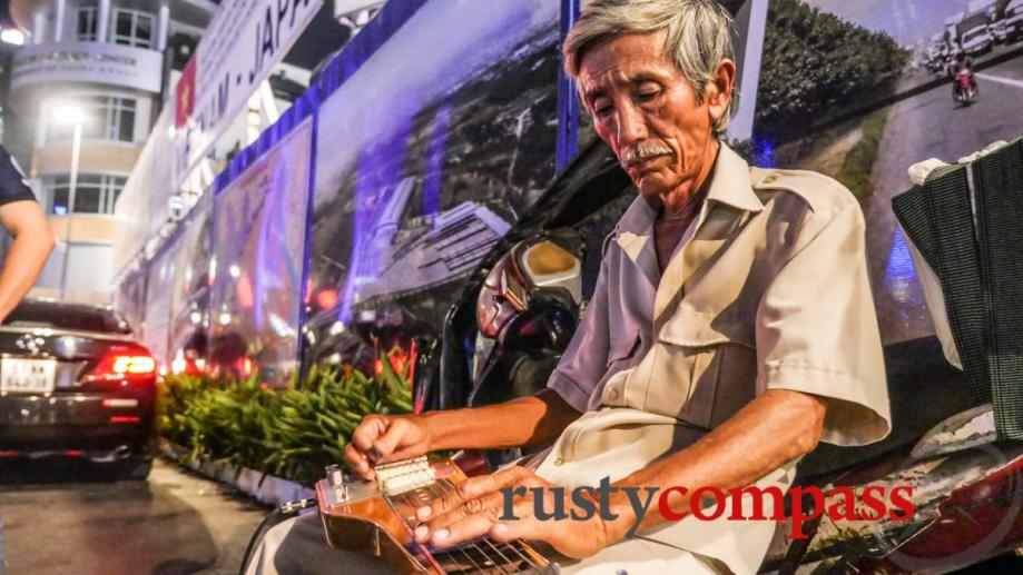Mournful slide guitar bounces around Saigon's Nguyen Hue pedestrian street.