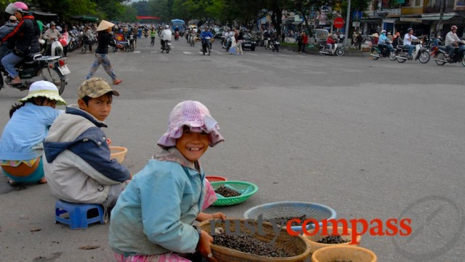 Kids selling small river snails near Dong Ba bridge, Hue