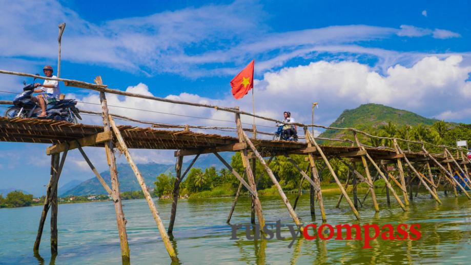 An old wooden bridge between 2 small villages along a...