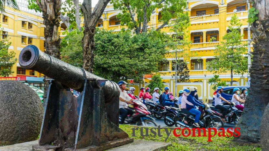 Cannons on the waterfront. Saigon with old French building in...